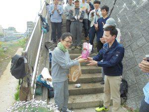 異動となった前区政推進課長の田中さんに1年半一緒に作業の汗を流した学生より感謝の花束贈呈